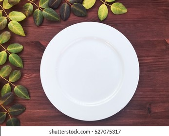 Empty white plat on the wooden brown background, top view