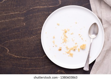 Empty white plate with crumbs on dark wooden background, top view
