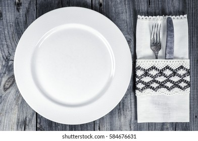 Empty white plate with cutlery, top view