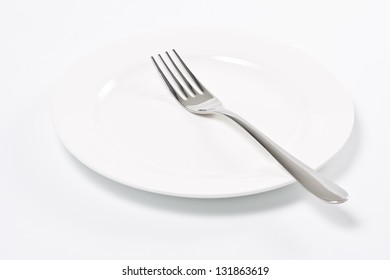 Empty white plate and fork.