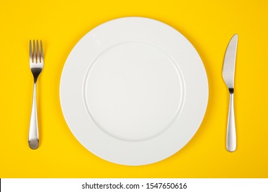 Empty white plate, fork and knife on yellow background