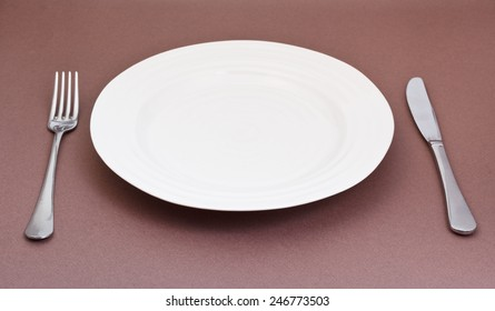 empty white plate with fork and knife on brown background