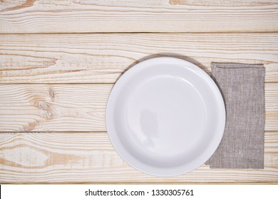 Empty white plate and  gray napkin on a wooden background, with copy space.