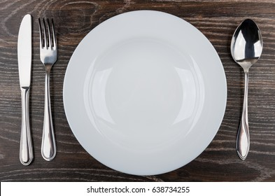 Empty white plate, knife, fork and spoon on wooden table. Top view