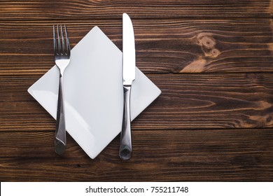 Empty white plate with knife and fork. view from top
