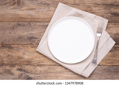 Empty white plate with napkin and silver cutlery on old wooden table, top view
