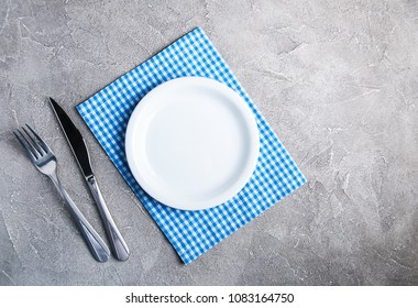 Empty white plate with nupkin on a gray stone background