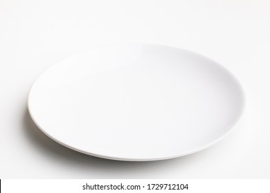 An empty white plate on white background.
