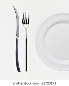 empty white plate on white background with  knife fork
