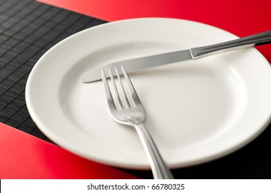 empty white plate on black table with knife and fork on the plate and red napkins by the sides of the plate