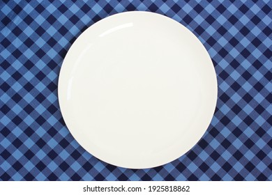 an empty white plate on a blue checkered tablecloth, top view. space for your text or object.  flat lay.