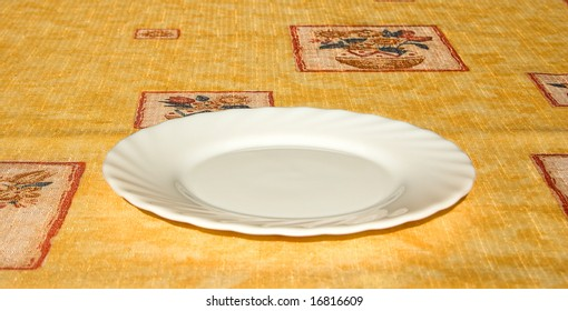 Empty white plate on bright yellow tablecloth
