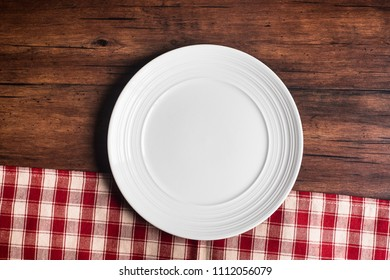 Empty white plate on a checkered red napkin on an old wooden brown background, top view. Image with copy space. Kitchen table with a towel and a plate - top view with copy space.