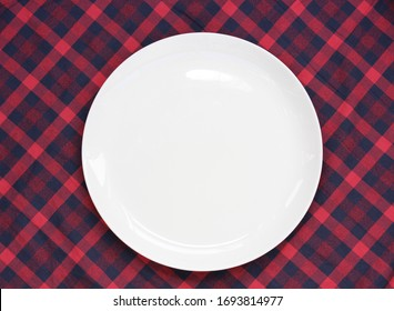 empty white plate on a red plaid background, top view. space for editing your text or image. mockup, template, and layout. tableware and checkered tablecloth, flat lay.