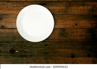 Empty white plate on wood background, top view