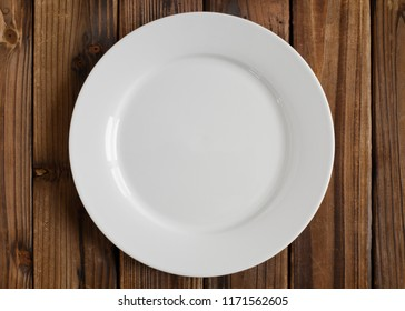 Empty white plate on wood. From above view.