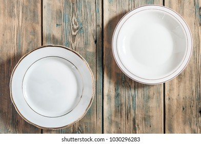 Empty white plate on wooden table. View from above