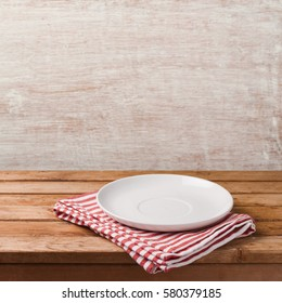 Empty white plate on wooden table over rustic background