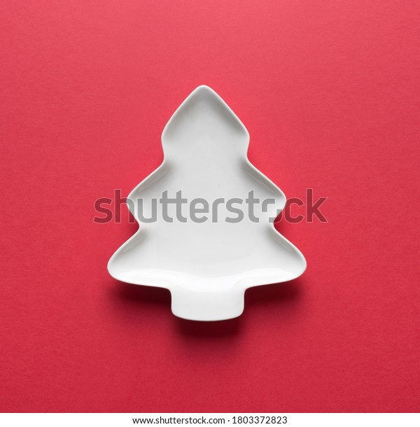 Empty white plate in shaped of Christmas tree on red with space for design. Xmas greeting card. View from above.