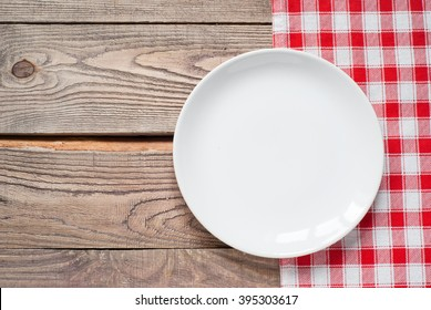 Empty white plate at wooden table. View from above with copy space