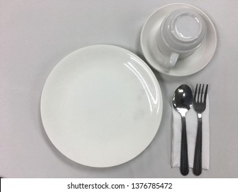 Empty white plates and glasses on a table with a set of tables and tissues on the table.