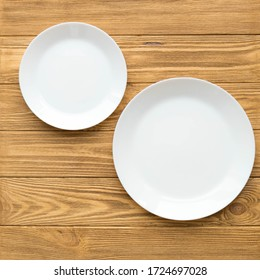 Empty white plates on a brown wooden table, square snapshot