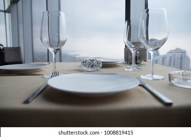 Empty white Plates on table at a restaurant with a large window view.