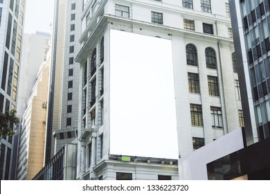 Empty white poster on city building. Public ad and commercial concept. Mock up