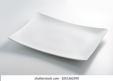 Empty white rectangular plate isolated on white table