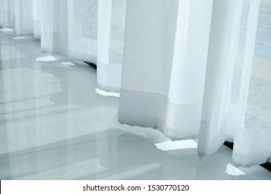 Empty white room with curtains on windows, white room interior with waving curtain by fresh air, White curtain blown by wind and gray color ceramic floor tiles texture.