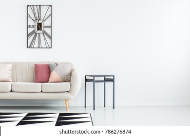 Empty white room with grey sofa, pink cushions, a table, metal clock and black and white carpet on the left