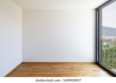 Empty white room with light parquet and window overlooking Lake Maggiore. Nobody inside