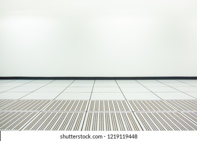 Empty white room with neon lights and white walls. Raised floor and suction tool in modern interior of server room in data center. White office room with tiled ceiling with neon lamps.