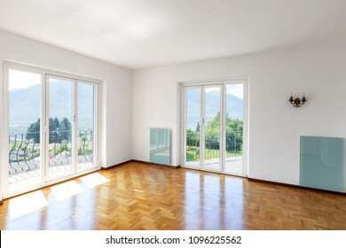 Empty white room with parquet and large windows overlooking the Swiss hills. Nobody inside