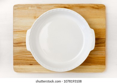 Empty white round baking pan on the wooden tray staying on the white wooden table