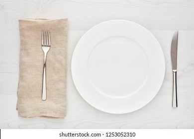 Empty white round ceramic plate, fork, knife and napkin on white wooden table. Top down view.