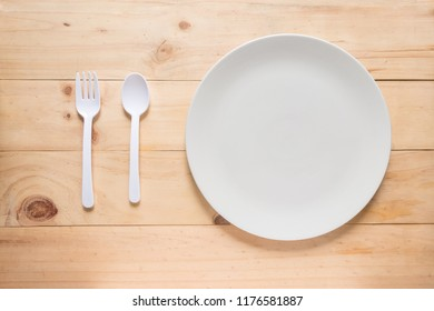 Empty white round dish or plate on wooden background, top view of tableware with copy space, spoon and fork