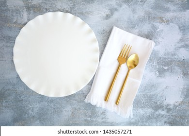 Empty white ruffled round plate with gold cutlery and white napkin on rough grey and white wooden background.  Dining concept in flat lay with copy space.