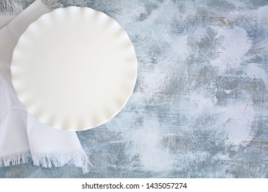 Empty white ruffled round plate and white napkin on rough grey and white wooden background.  Dining concept in flat lay with copy space.