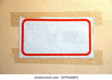 Empty white sheet of paper with a red frame. Glued tape to the wall.