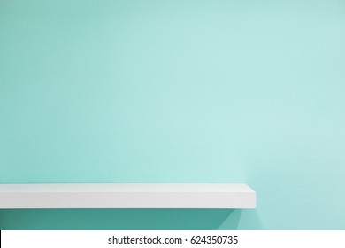 Empty white shop shelf, retail shelf on green vintage background.