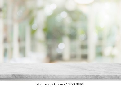 Empty white stone marble table top and blurred of interior room with window view green from tree garden background background - can used for display or montage your products.