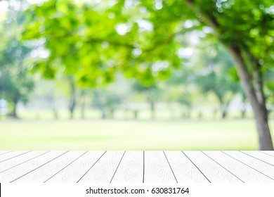 Empty white table, perspective wood over blur trees with bokeh background, product display montage background