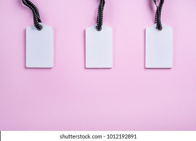Empty white tags in a row on pink background. Top view. Mock up sample. Blank price tag. Design for shopping label template, discount, Sale. Sales tags.