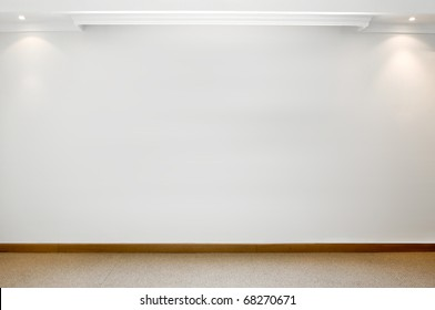 Empty white wall with 2 spot lights and carpeted floor