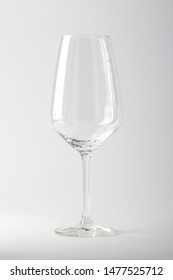 Empty white wine glass on white backdrop