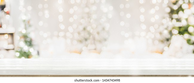 Empty white wold table top with abstract warm living room decor with christmas tree string light blur background with snow,Holiday backdrop,Mock up banner for display of advertise product