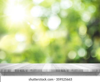 Empty white wood table top with blur green tree bokeh background, Template mock up for montage of product