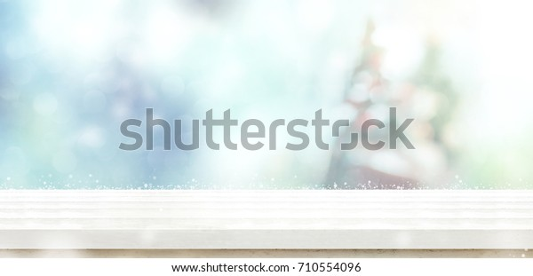 Empty white wooden table top with abstract muted blur christmas tree and snow fall background with bokeh light,Holiday backdrop,Mock up banner for display or montage of product.