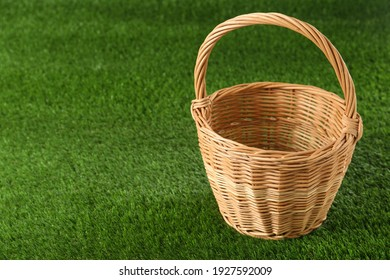 Empty wicker basket on green lawn, space for text. Easter item